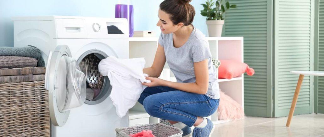 Frau holt die gewaschene Wäsche aus der Maschine