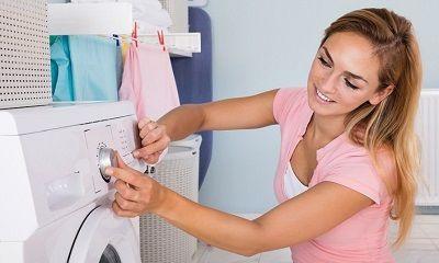 Junge Frau bedient die Waschmaschine