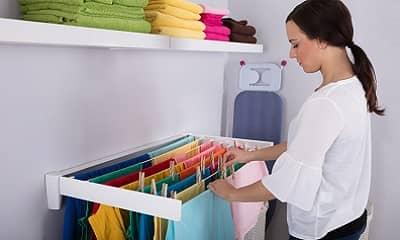 Frau hängt Wäsche zum Trocknen in der Wohnung auf